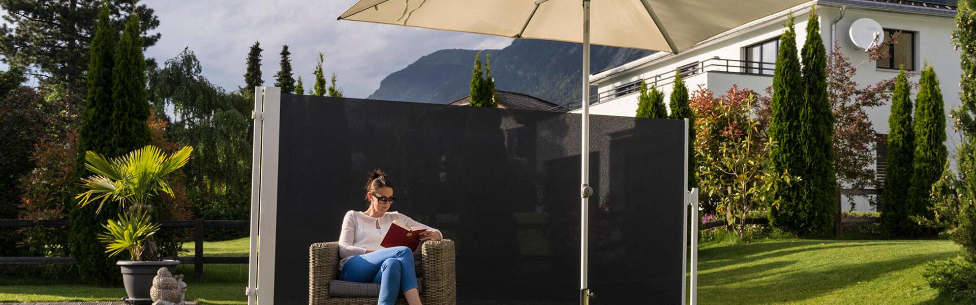 Eine Frau liest in ihrem Garten hinter einem Sichtschutz ungestört ein Buch.