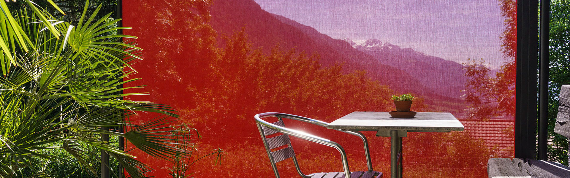Strahlend rotes Windschutztuch in einem mediterranen Garten.
