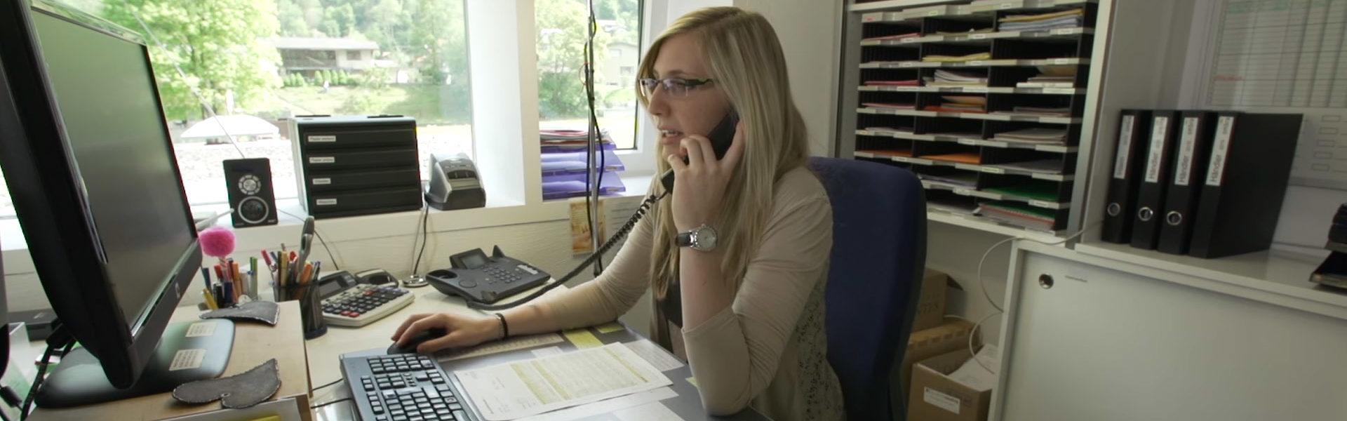 Eine Mitarbeiterin von ombra sitzt an ihrem Schreibtisch und beantwortet eine Kundenanfrage per Telefon.