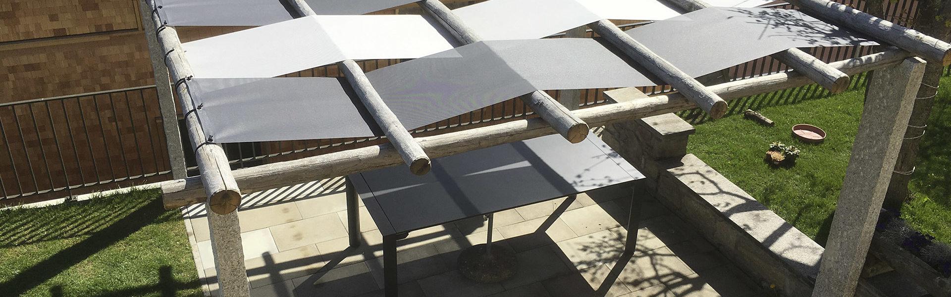 Sonnentücher mit Ösen über einem Sitzplatz montiert.