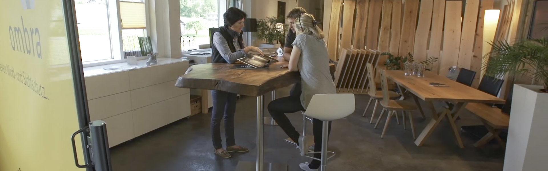 Eine Frau zeigt ihren beiden Kunden die verschiedenen Ausführungen der ombra Wind- und Sichtschutzsysteme.